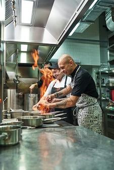 Chef e dois assistentes preparando o prato no fogão com lareira na cozinha