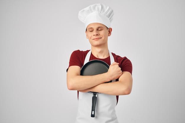 Chef em frigideira uniforme nas mãos de uma cozinha profissional de restaurante