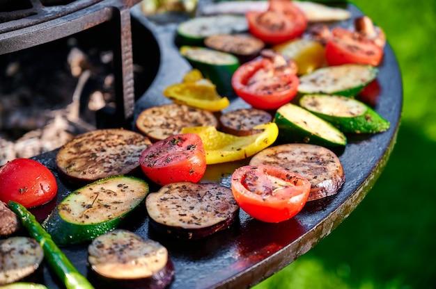 Chef em luvas de borracha frita legumes na grelha