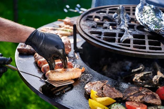 Chef em luvas de borracha frita salsichas na grelha