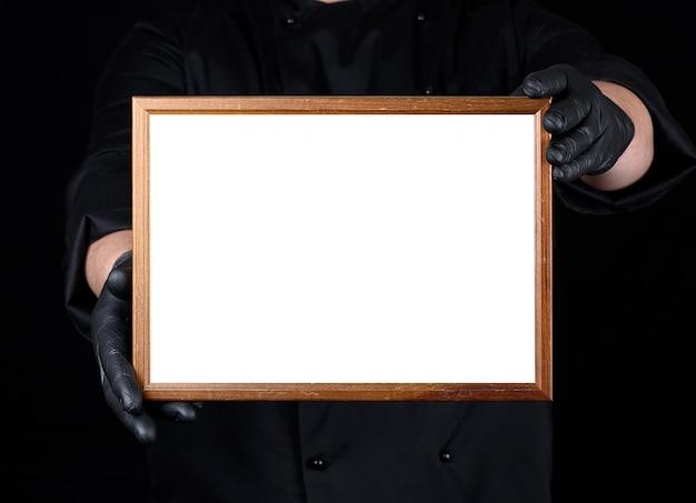 Chef em luvas de látex pretas e pretas uniformes segurando uma moldura de madeira com branco espaço vazio