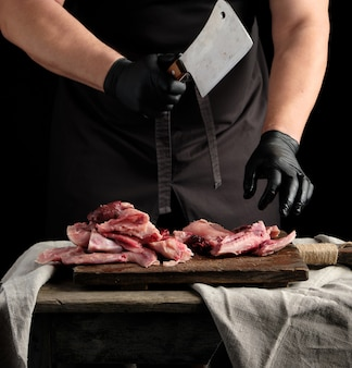 Chef em luvas de látex pretas segura uma faca grande e corta em pedaços de carne de coelho crua