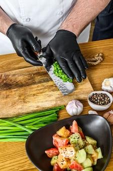 Chef em luvas pretas prepara uma salada de vegetais vegatariana