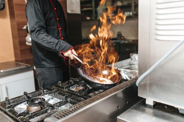 Chef em restaurante de cozinha preparando vegetais com fogo