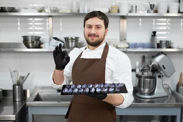 Chef em uma cozinha profissional segura chocolates artesanais nas mãos e mostra o sinal de ok