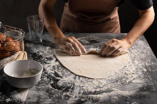 Chef enrolando massa para fazer pastéis