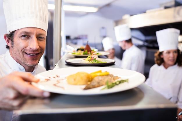 Chef entregando pratos pela estação de pedidos