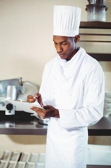 Chef escrevendo notas sobre uma prancheta