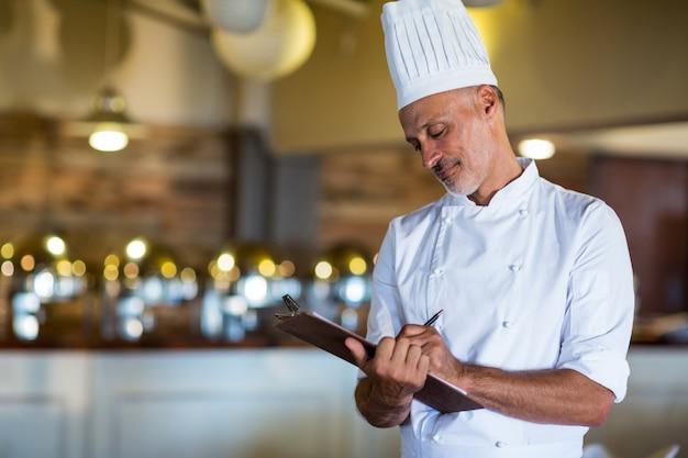 Chef, escrevendo sobre uma prancheta