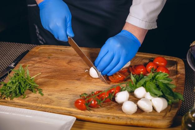 Chef está cozinhando um prato gourmet de mussarela com manjericão, tomate cereja e rúcula.