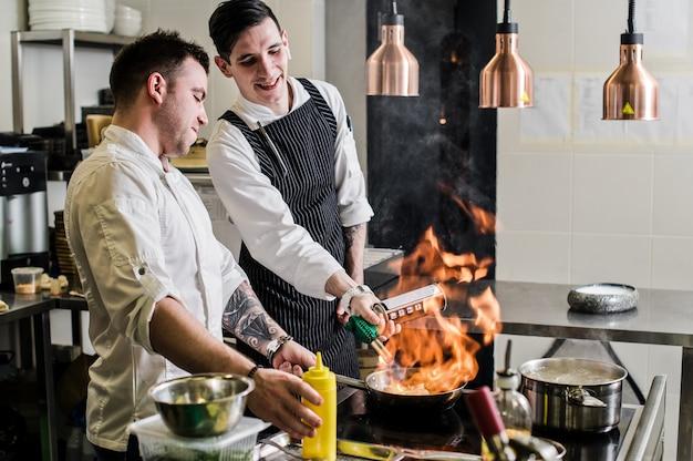 Chef está fazendo flambe em uma cozinha de restaurante