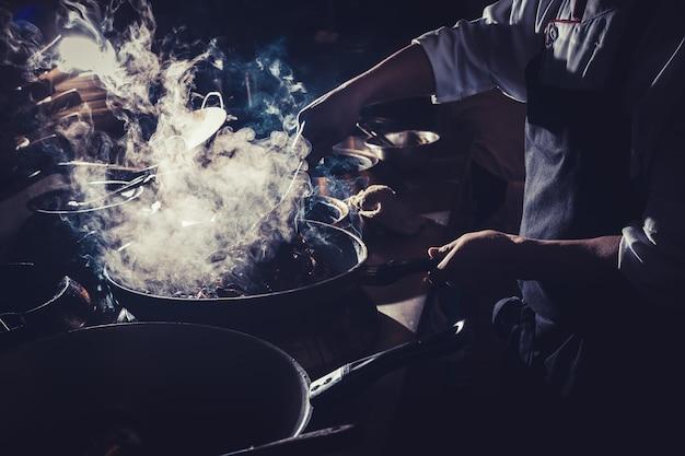 Chef está mexendo legumes no wok