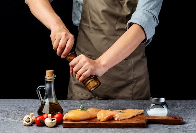 Chef está moendo pimenta para marinar o peito de frango
