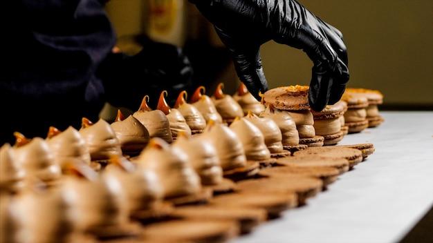 Chef está montando macarons de caramelo. close-up da mão na luva é coloca uma concha em biscoitos franceses.