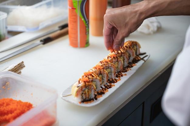 Chef está polvilhando sobre salmão defumado e rolos de queijo