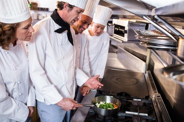 Chef experiente, explicando aos colegas na cozinha