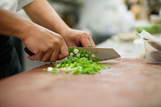 Chef fatiar legumes na superfície de madeira, comida,
