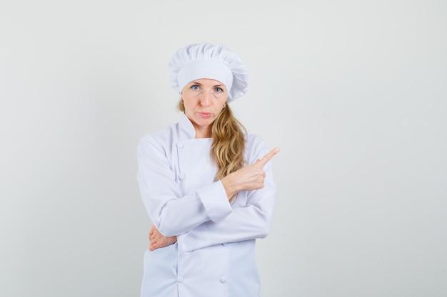 Chef feminina apontando para longe em um uniforme branco e parecendo em dúvida