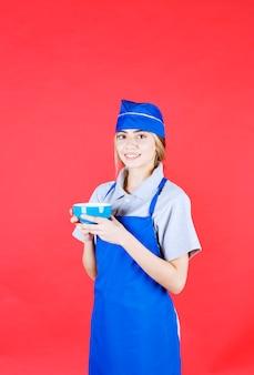 Chef feminina com avental azul segurando uma xícara de macarrão