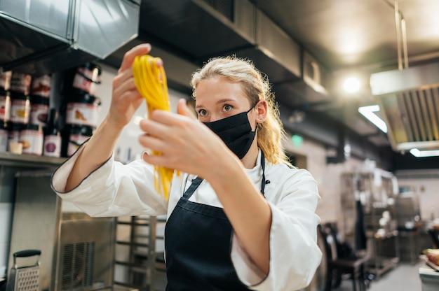 Chef feminina com máscara segurando macarrão fresco
