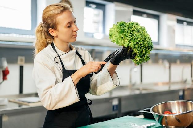 Chef feminina comprando salada na cozinha