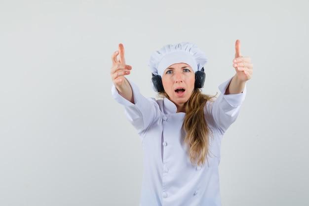 Chef feminina convidando para vir usando fones de ouvido em uniforme branco
