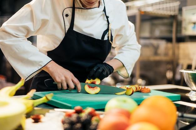 Chef feminina cortando pêssego com luva