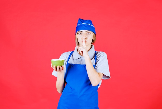 Chef feminina de avental azul segurando uma xícara de macarrão verde e pedindo silêncio