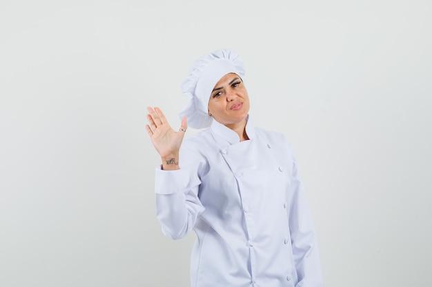 Chef feminina de uniforme branco acenando com a mão para cumprimentar e parecer confiante