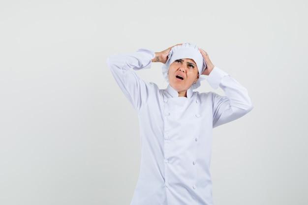 Chef feminina de uniforme branco com as mãos na cabeça e parecendo melancólica