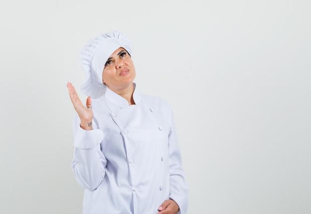 Chef feminina de uniforme branco levantando a mão, olhando para cima e parecendo pensativa