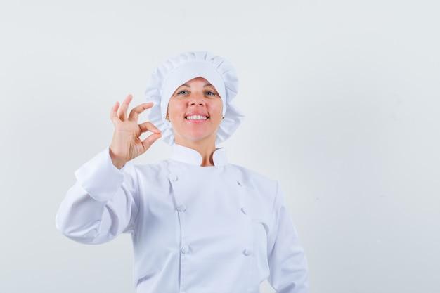 Chef feminina de uniforme branco, mostrando um gesto de aprovação e parecendo confiante