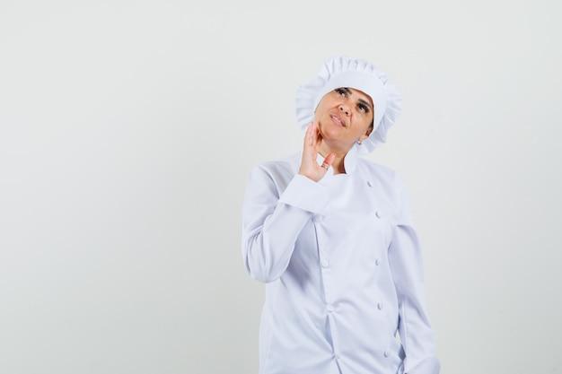 Chef feminina de uniforme branco olhando para cima e parecendo pensativa