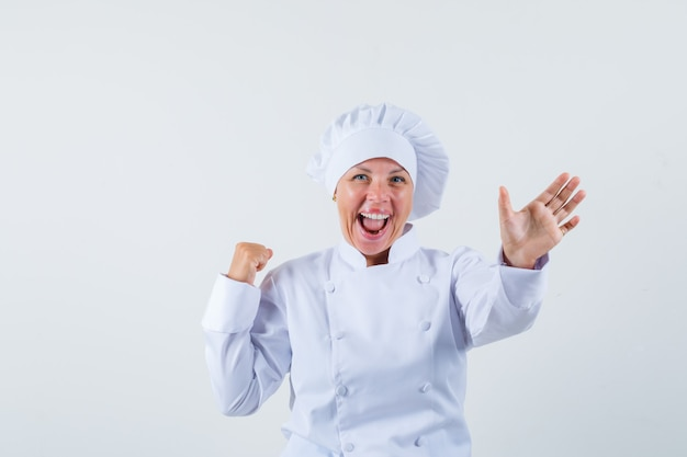 Chef feminina de uniforme branco posando para mostrar sua nova receita de refeição e parecendo otimista
