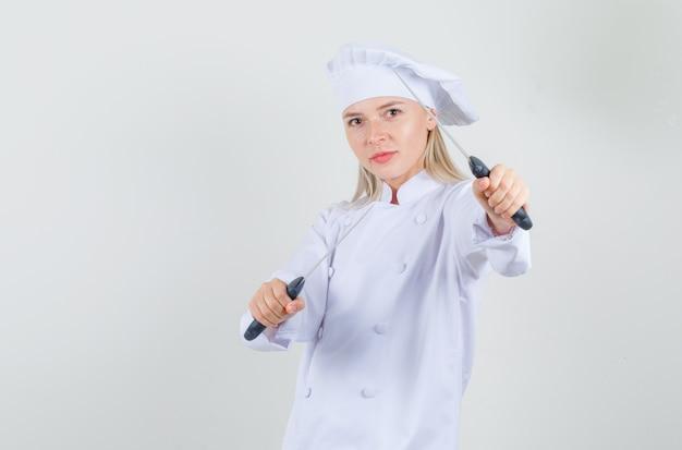 Chef feminina de uniforme branco segurando facas em pose de boxeador e parecendo feliz