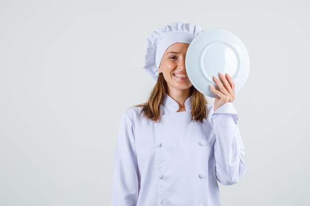 Chef feminina de uniforme branco segurando o prato perto do rosto e parecendo feliz