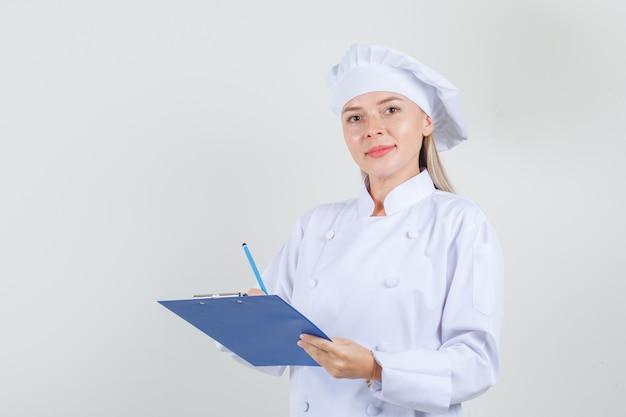 Chef feminina de uniforme branco segurando um lápis e uma prancheta e parecendo alegre