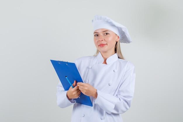 Chef feminina de uniforme branco segurando uma prancheta e um lápis e parecendo feliz