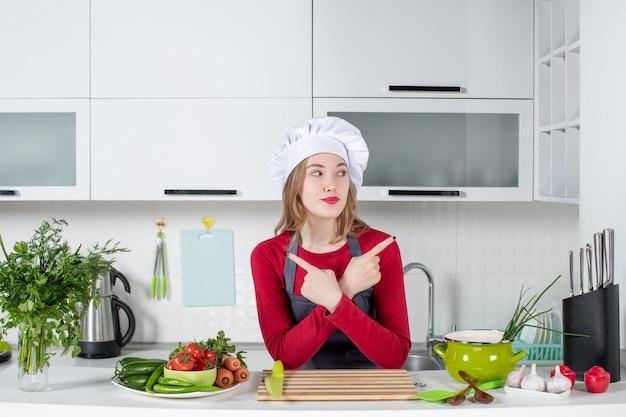 Chef feminina de uniforme em pé atrás da mesa da cozinha, cruzando as mãos