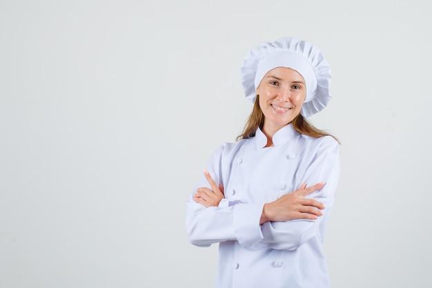 Chef feminina em pé com os braços cruzados em um uniforme branco e parecendo feliz