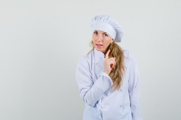 Chef feminina em uniforme branco avisando com o dedo levantado e olhando séria