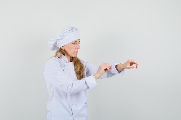 Chef feminina em uniforme branco enrolando a manga e olhando com cuidado