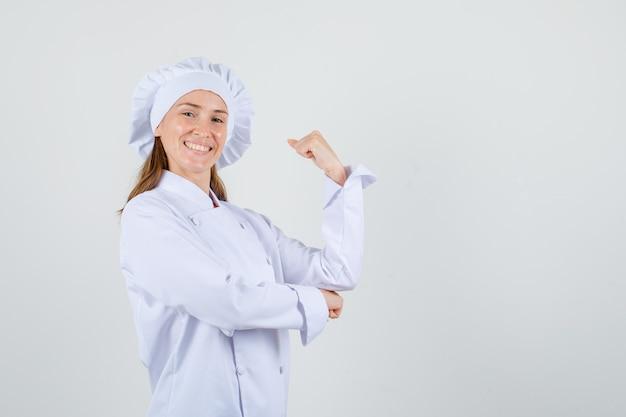 Chef feminina em uniforme branco, mostrando o braço com o punho cerrado e parecendo alegre