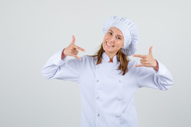 Chef feminina em uniforme branco, mostrando o gesto de 'eu te amo' e parecendo alegre