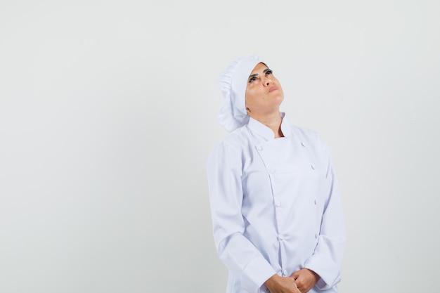 Chef feminina em uniforme branco olhando para cima e parecendo focada
