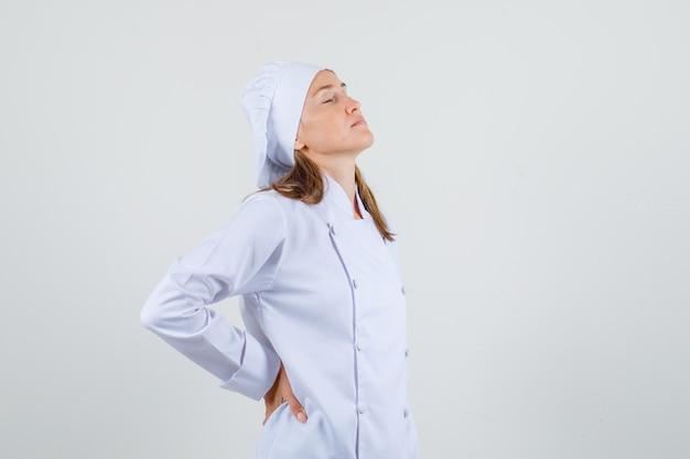 Chef feminina em uniforme branco, sofrendo de dores nas costas e parecendo cansada.