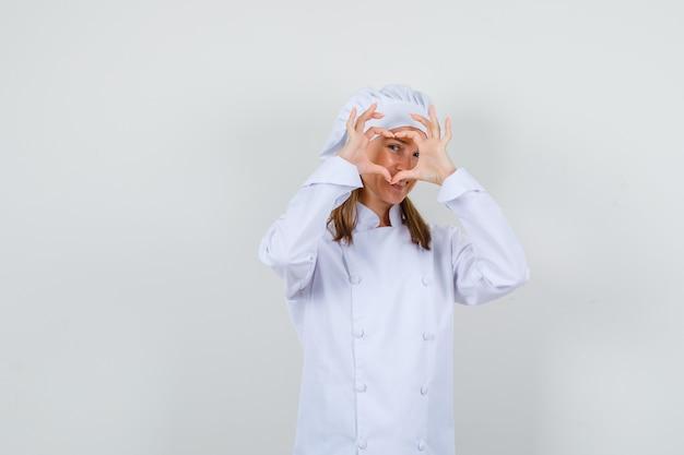 Chef feminina fazendo formato de coração em uniforme branco e parecendo feliz