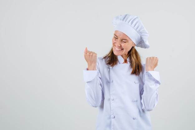 Chef feminina mostrando gesto de vencedor em uniforme branco e parecendo feliz