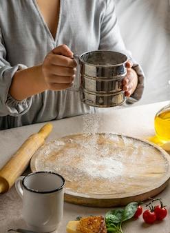 Chef feminina peneirando farinha sobre uma placa de madeira para enrolar a massa da pizza