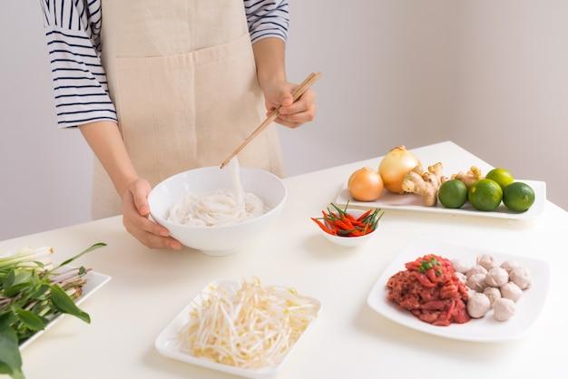 Chef feminina prepara sopa vietnamita tradicional pho bo com ervas, carne e macarrão de arroz